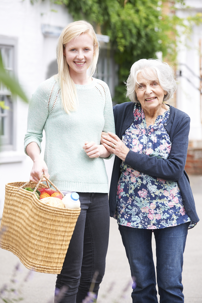 A young woman accompanying an elderly woman shopping